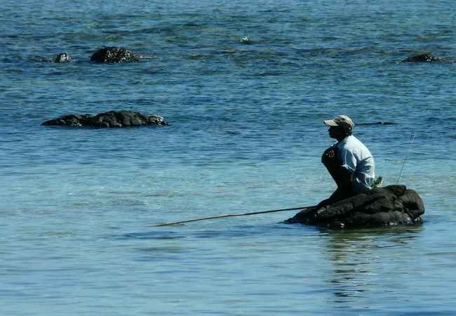 fisherman fishing from a rock in the lagoon