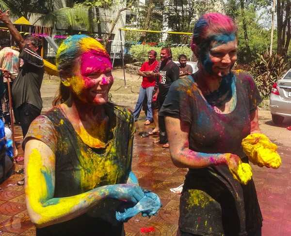 People covered with coloured powder at Holi