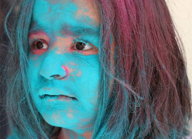 Child face smeared with coloured powder at Holi