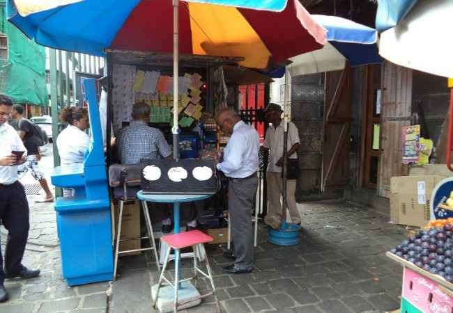 Lottery ticket vendor in his pavement shop Port Louis